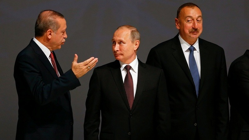 Turkish President Erdogan chats with his Russian counterpart Putin as Azeri President Aliyev watches during the 23rd World Energy Conress in Istanbul