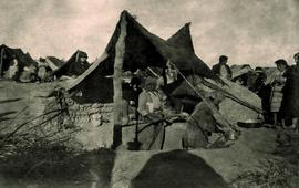 Фотография сделана немецким офицером в 1915/1916 г. Об этом свидетельствует машинописная фраза на обороте, на немецком языке: «Армянский лагерь в Ракке». На снимке ясно видно ужасное состояние армянских беженцев. Под палящим солнцем, прилагая последние усилия и возможности, армянские беженцы соорудили хлебопекарню, используя все, что было под рукой.